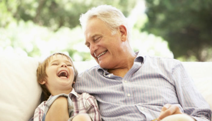 Young boy and elderly man laughing